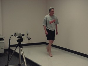 A person being analysed in a small scale video gait analysis setup
